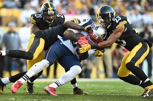 The Steelers' Mike Mitchell, right, and Robert Golden take down the Patriots' LeGarrette Blount at Heinz Field Sunday.