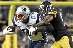 New England Patriots tight end Rob Gronkowski catches a pass in front of linebacker Lawrence Timmons last season.