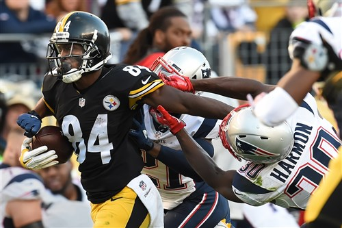The Steelers' Antonio Brown fights off Patriots tacklers in the second quarter at Heinz Field Sunday.