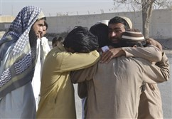 Pakistani family members of victims mourn outside a police training center where gunmen opened fire, in Quetta, Pakistan, Tuesday.