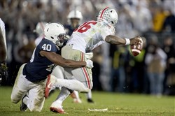 Penn State linebacker Jason Cabinda tackles Ohio State quarterback J.T. Barrett during the Nittany Lions upset of the Buckeyes earlier this season. Cabinda, the team's signal caller on defens, said on Wednesday he is returning to Penn State for his senior season.