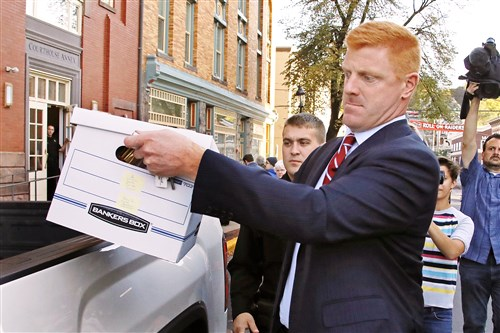 Former Penn State University assistant football coach Mike McQueary, center, leaves the Centre County Courthouse in Bellefonte, Pa.