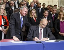 State Sen. John Wozniak, D-Cambria, stands next to Pennsylvania Gov. Tom Wolf in the state Capitol Rotunda in Harrisburg on Wednesay as Mr. Wolf signs a package of bills to fight the opioid and heroin crisis.