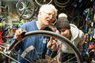 Jerry Kraynick, left, helps customer Abby Perrott, 23, of Friendship, with her bike wheel at Kraynick's Bike Shop along Penn Avenue in Garfield Tuesday. Mr. Kraynick not only provides three floors of miscellaneous bike parts for sale, but also helps teach people how to repair and care for their bikes and has spaces for customers to work on their bikes as well.