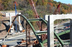 Construction workers on Saturday place steel arches and decking over the Parkway East as part of the Greenfield Bridge project.