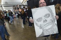 Artist Chad Susan from North Carolina, holding a portrait of Evan Peters in one of his acting roles, waits in line for an autograph at the Wizard World Comic Con, held Nov. 6, 2016, at the David L. Lawrence Convention Center.