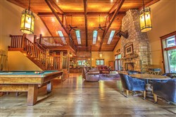 The lodge features pine and oak ceiling trusses and a tall stone fireplace.