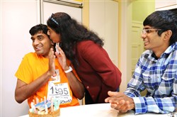 Chitra Sharathchandra gives a kiss to her son Tejus as his brother Akshay,17,  looks on during the celebration of Tejus' 21st birthday at their home in Squirrel Hill.