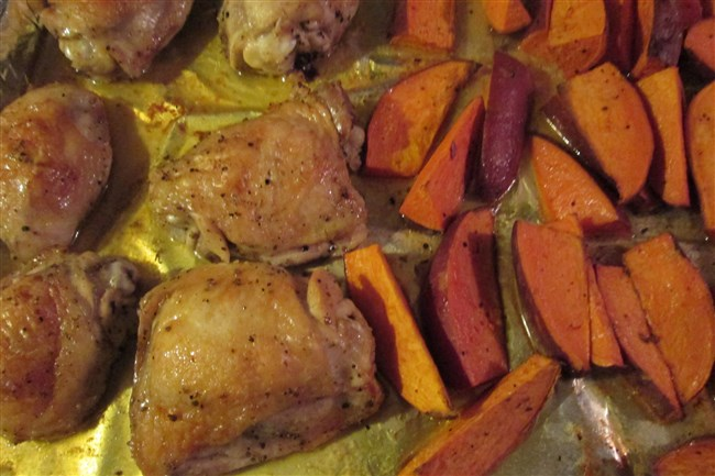 Sweet potatoes and chicken thighs are baked at the same time, in the same sheet pan, saving stress and clean-up.
