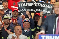 In this May 5, 2016 photo, Coal miners wave signs as Donald Trump speaks during a rally in Charleston, W.Va. Trump's election could signal the end of many of President Barack Obama's signature environmental initiatives.
