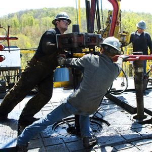 In this April 23, 2010 photo, workers move a section of well casing into place at a Chesapeake Energy natural gas well site near Burlington, Pa., in Bradford County.