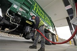 Waste Management driver Alan Sadler fills his truck with CNG gas at the company's filling station in Washington County. The Port Authority of Allegheny County expects to roll out new buses, powered by natural gas or electricity instead of diesel, in the next three years.