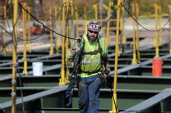 A worker with Amelie Construction walks Tuesday along the deck of the Greenfield Bridge, which remains under construction.