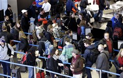 In this Nov. 29, 2015, file photo, travelers line up at a security checkpoint at O'Hare International Airport in Chicago. The auto club AAA said today that it expects 1 million more Americans to venture at least 50 miles from home, a 1.9 percent increase over last year.