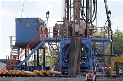 In this June, 2012 file photo, a crew works on a gas drilling rig at a well site for shale based natural gas in Zelienople, Pa.