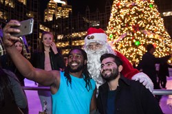 Yaseen Barnawi, left, 23, of Moon Township, takes a selfie in an unseasonably breezy shirt with his friend, Mohammed Alibi, right, 23, both of Moon Township, and Santa at the PPG Place skating rink during Comcast Light Up Night.