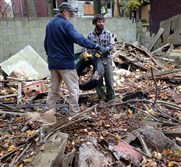 Joe Divack, left, and Dave Yake, both of Allegheny CleanWays, survey yet another dump site to clear out of Stoner Way in Wilkinsburg.