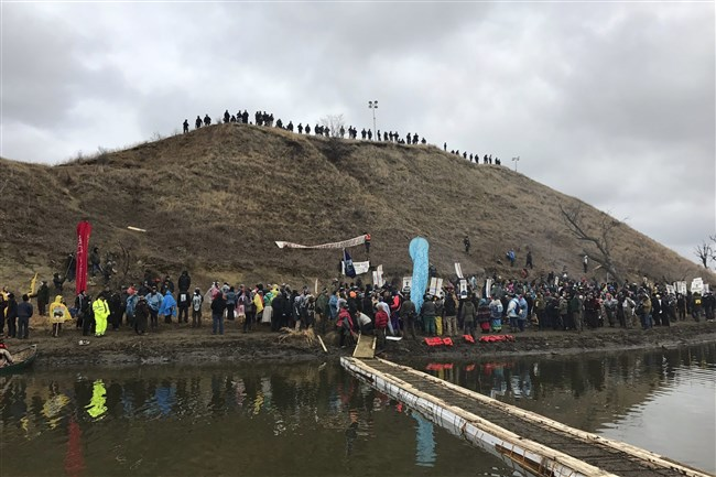 Protesters against the Dakota Access oil pipeline gather at and around a hill, referred to as Turtle Island, where demonstrators claim burial sites are located, Thursday, Nov. 24, 2016 in Cannon Ball, N.D. The hill is across a body of water from where hundreds and times thousands of people have camped out for months to protest the construction of the four-state pipeline.