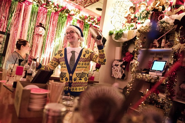Bartender Elliot Sussman of Friendship laughs as he shakes up some holiday-themed cocktails at the new pop up bar Miracle in Downtown on Tuesday evening, Nov. 30, 2016.