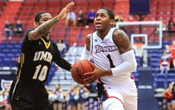 Duquesne's Mike Lewis II drives past a Maryland Baltimore County defender during a game last November. Lewis was named to the A-10 preseason third-team Tuesday.