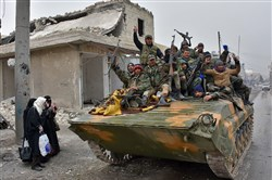 Syrian pro-government forces sit on a military vehicle driving past residents fleeing the eastern part of Aleppo and gathering in Masaken Hanano, a former rebel-held district that was retaken by the regime forces last week, on Wednesday.