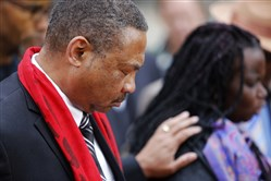 Pastor Thomas Dixon, left, prays during a vigil in front of the Charleston County Courthouse on Monday as the jury deliberated in the Michael Slager trial.