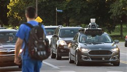 An UBER Self Driving Ford Fusion sits at a redlight on Beechwood Boulevard  and waits to turn onto 5th Avenue in August 2016.