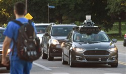 A self-driving Uber vehicle sits at a red light on Beechwood Boulevard in August.