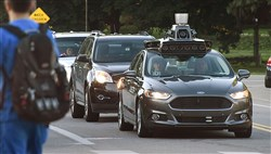 An Uber self-driving Ford Fusion sits at a redlight on Beechwood Boulevard in Squirrel Hill.
