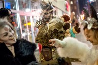 "Jamie Agpar, 31, of East Liberty, lights his pipe as he waits for his fellow Krampus-attired revelers to leave a bar Downtown in 2016. ""Pittsburgh people should be attracted to this and love it because we love Halloween, we're crazy about Christmas, and this is a little bit of both,"" said organizer Mark Menold of hitting the town in the Krampus tradition, which stems from European Christmas folklore. ""It bridges that lull in between. There's no presents and there's no family and stress."""