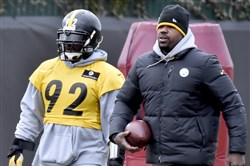 Steelers linebacker James Harrison walks with outside linebackers coach Joey Porter during practice in December on the South Side.