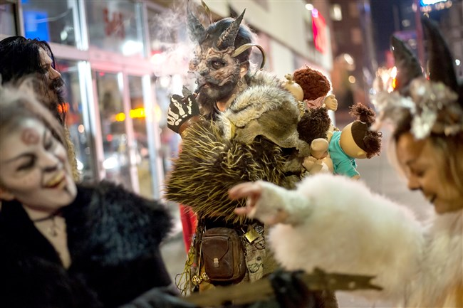 """Jamie Agpar, 31, of East Liberty, lights his pipe as he waits for his fellow Krampus-attired revelers to leave a bar Downtown in 2016. """"Pittsburgh people should be attracted to this and love it because we love Halloween, we're crazy about Christmas, and this is a little bit of both,"""" said organizer Mark Menold of hitting the town in the Krampus tradition, which stems from European Christmas folklore. """"It bridges that lull in between. There's no presents and there's no family and stress."""""""