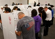 A voter wears a shirt with words from the United States Constitution while casting his ballot early as long lines of voters cast ballots at the San Diego County Elections Office in San Diego, California, U.S., Nov. 7.