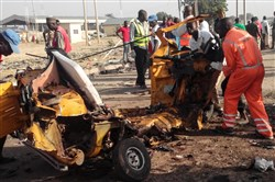 This file photo taken on Oct. 29 shows emergency personnel standing near the wrecked remains of a vehicle ripped apart following two suicide bombings in Nigeria's northeast city of Maiduguri where at least nine people were killed and scores of others were injured.