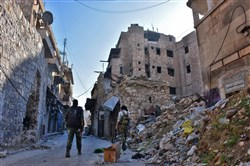 Syrian pro-government forces walk past rubble in old Aleppo on Friday.
