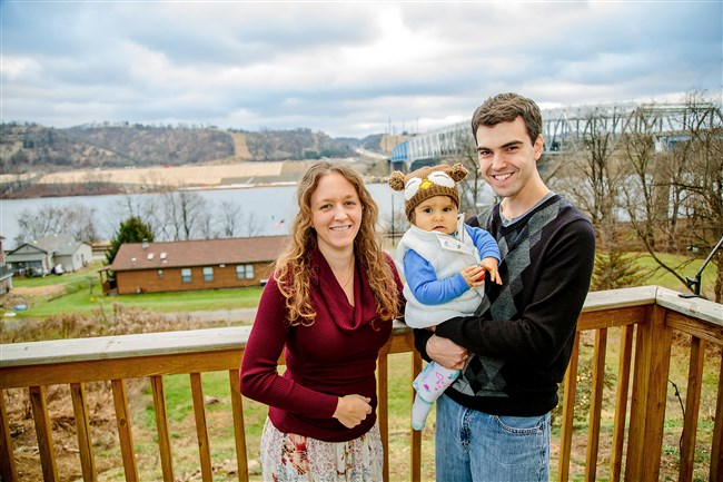 Dan and Gina Rubino with their 1-year-old daughter, Maria, on the back porch of their Vanport home. The couple's house overlooks the Ohio River and the site of Shell's planned ethane cracker plant.