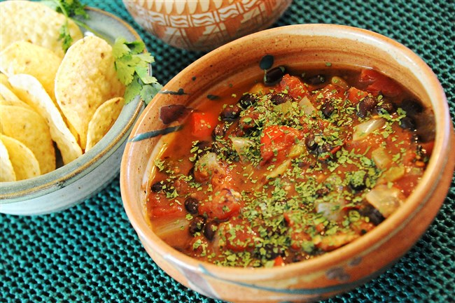Black bean soup dusted with cilantro, served with tortilla chips on the side.
