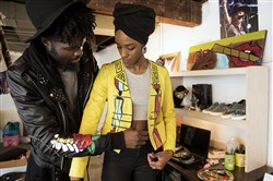 Christian Diboko, creator of fashion brand ProBantuStyle, helps his fiance, Binay Geathers, put on one of his jackets at his home studio in Whitehall in December. Geathers regularly models his designs and helps to get his brand up and running.