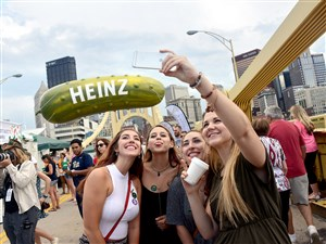 From left, Abby Williams of Ligonier, Nina Clarke of Squirrel Hill, Ashley Barone of Sidman and Jennifer Seniuk of Alberta, Canada, take a selfie in front of the 35-foot Heinz pickle balloon at Picklesburgh in 2016.