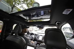Devin Greene sits in the front seat of an Uber driverless car during a test drive in San Francisco. Uber has pulled its self-driving cars from California roads.
