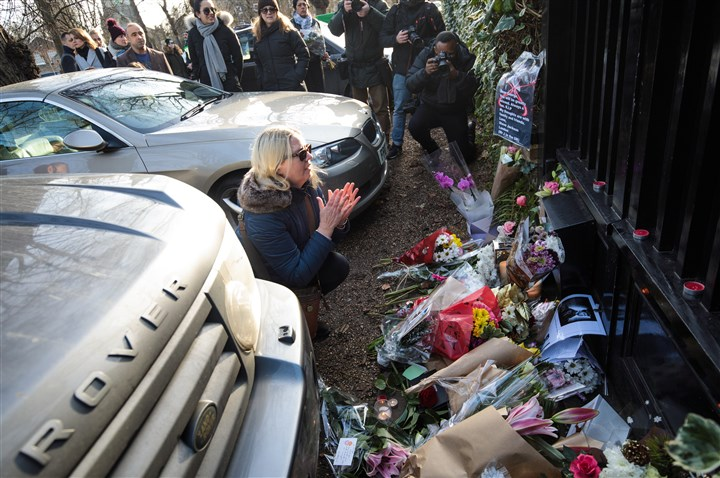 Tributes After The Death Of Music Icon George Michael-1 A woman gestures as she leaves tributes of flowers at the home of pop music icon George Michael in The Grove, Highgate on Monday in London.