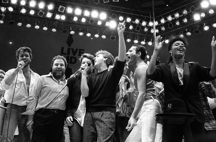 George Michael Obit-15 In this July 13, 1985, file photo, from left, George Michael of Wham!, concert promoter Harvey Goldsmith, Bono of U2, Paul McCartney, concert organizer Bob Geldof and Freddie Mercury of Queen join in the finale of the Live Aid famine relief concert, at Wembley Stadium, London.