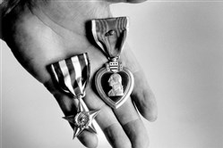 "In this file photo from 1994, James ""Harper"" Jordan holds two of the medals -- a Silver Star and a Purple Heart -- he earned fighting on Omaha Beach on D-Day."