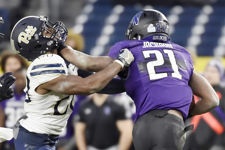 WEB pinstripe bowl pix Northwestern's Justin Jackson pushes away Pitt's Dennis Briggs as he carries in the third quarter Wednesday in the Pinstripe Bowl. Northwestern players have been at the forefront of a movement to unionize college athletes.