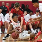 Fox Chapel's Ben Kelly reaches over Penn Hills' Myles Yarborough as they fight for the basketball Tuesday night. Penn Hills won the battle of unbeatens, 62-59.