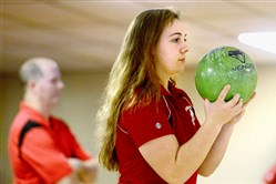 Sarah Helffrich, a member of the Avonworth girls bowling team, prepares to bowl in a match Dec. 7 at Pines Plaza Lanes. Coach Jeff Schoeppner is in the background.