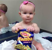 In this photo provided by the Carrie Stevenson, her daughter Estelle holds a bag of peanut snacks in her pediatrician's office at age 9 months in Columbus, Ohio. Most babies should start eating peanut-containing foods well before their first birthday, according to guidelines released today.