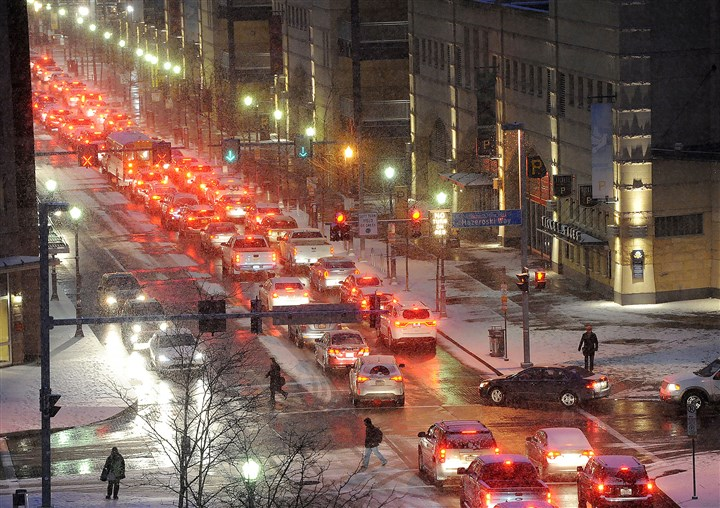 20170105rldSnowFalls02-1 Traffic backs up along General Robinson Drive by PNC Park as snow falls on the North Side.