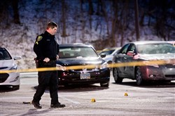 Cpl. Michael Lynch, with the Monroeville Police Department, examines tagged pieces of evidence following a shooting near the Monroeville Mall in the Macy's parking lot in Monroeville on Friday, Jan 6, 2017.