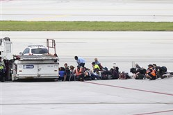Passengers wait on the tarmac at Fort Lauderdale-Hollywood International Airport, Friday, in Fort Lauderdale, Fla.   A gunman opened fire in the baggage claim area at the airport Friday, killing several people and wounding others before being taken into custody in an attack that sent panicked passengers running out of the terminal and onto the tarmac, authorities said.